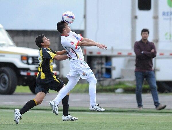 Joshua Villalobos (izquierda) lucha con el jugador del Belén FC, Roberto Rojas, al fondo se puede apreciar al técnico belemita Vinicio Alvarado. La lucha por el no descenso se pone emocionante a su estilo. | ADRIÁN SOTO