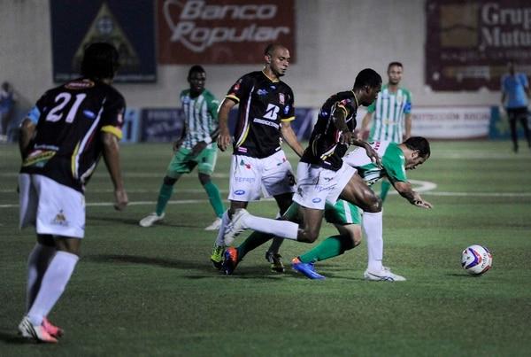 Los belemitas Heiner Mora y Roy Myrie (negro) marcador al jugador de Limón Bill González.