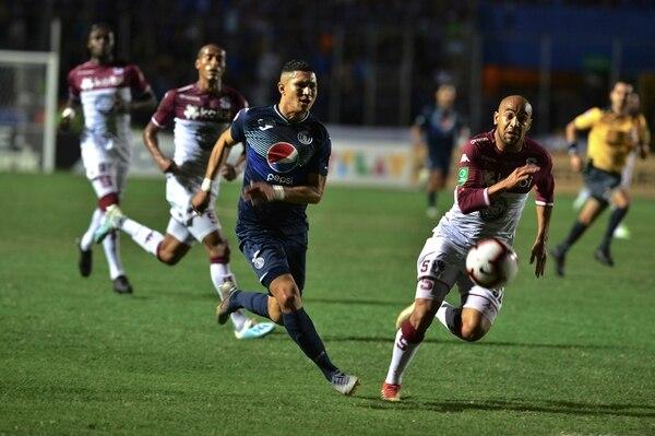 El jugador del Motagua Kevin López (izquierda) recibe la marca del zaguero morado Alexander Robinson (derecha). Foto: AFP