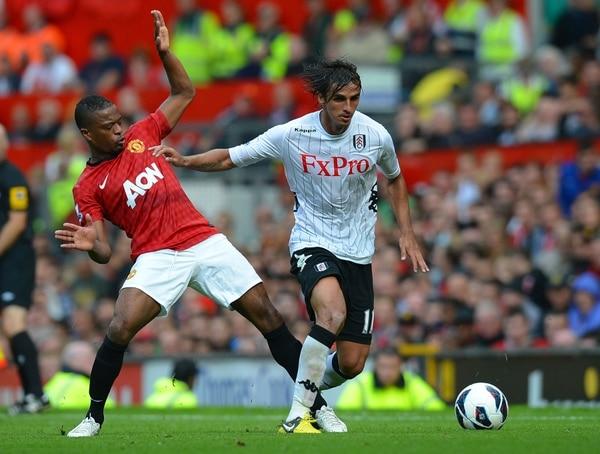 Bryan Ruiz con la camiseta del Fulham eludiendo la marca de Patrice Evra del Machester United.