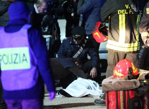 Un hombre toca un cuerpo sin vida en el suelo fuera de la discoteca Lanterna Azzurra en Corinaldo, Italia.