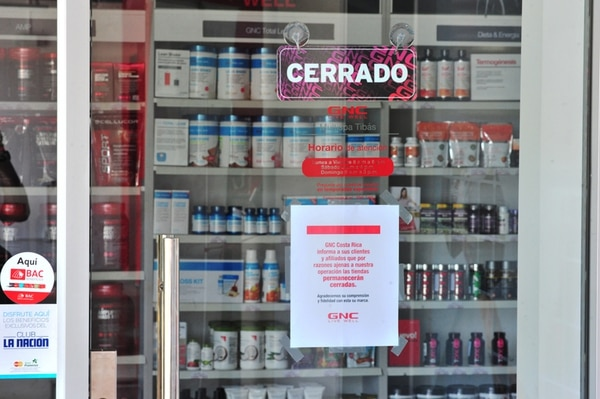 La sucursal de la tienda GNC de Tibás se encontraba cerrada ayer. La administración presentó esta nota explicativa a sus clientes.   JOSÉ RIVERA