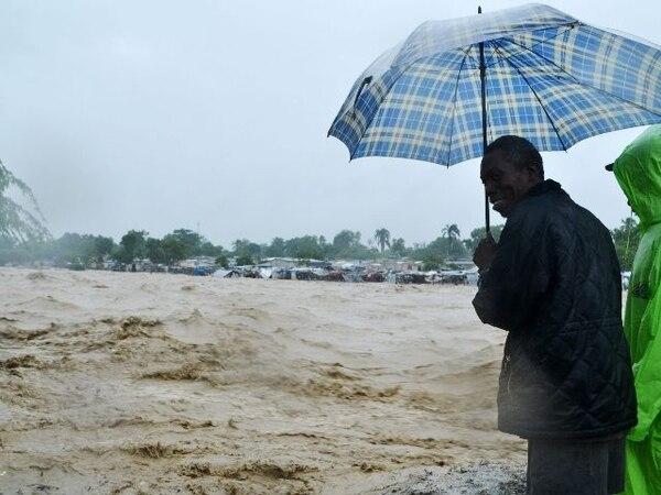 Pobladores de Haití se resguardan a la orillla de un río crecido. | AFP.