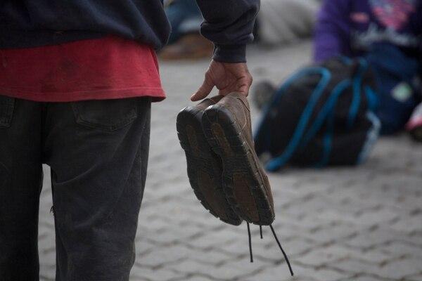 Un migrante hondureño cargaba sus zapatos poco antes de reemprender -el martes 16 de octubre del 2018- la caminata en Esquipulas, Guatemala, con rumbo a Estados Unidos.