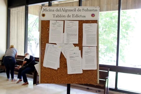 En una oficina pública en Bayamón se exhiben edictos sobre casas que están disponibles para ser subastadas.