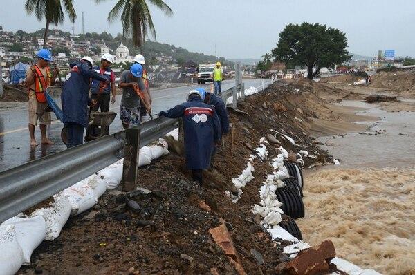 Trabajadores reforzaban el lunes con sacos de arena las bases de esta carretera que conduce al puerto turístico de Acapulco. | AP