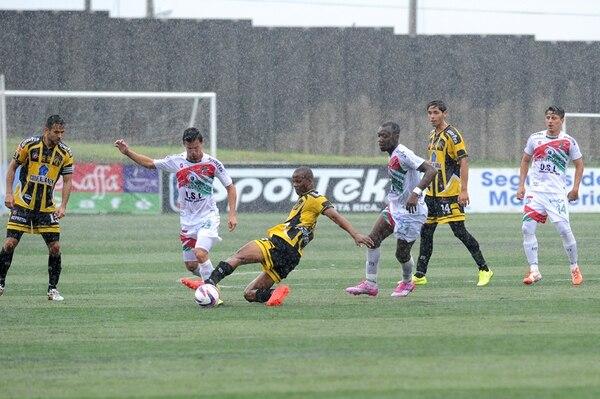 Rudy Dawson, defensor de Uruguay, se barre para tratar de quitarle la pelota a Víctor Chavarría, zaguero carmelo, en el juego de ayer. | MELISSA FERNÁNDEZ