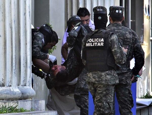 Policías militares acarreaban el cuerpo de un compañero asesinado durante el ataque de pandilleros, este jueves 13 de febrero del 2020 en la ciudad de El Progreso, norte de Honduras.