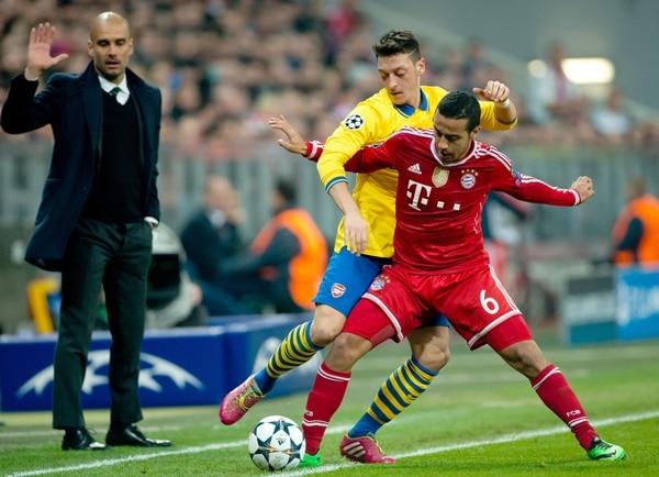 Thiago Alcantara del Bayern Munich ante Mesut Ozil del Arsenal este martes en juego por la Champions League.