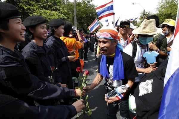 Mujeres policía regalan rosas a un manifestante a las puertas de la Casa del Gobierno en Bangkok.