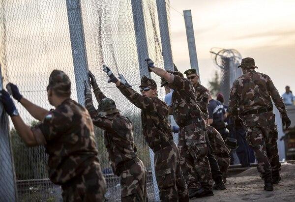 Varios soldados del ejército húngaro colocan una barrera tras cerrar la frontera con Serbia en Röszke, a 180 kilómetros de Budapest, Hungría