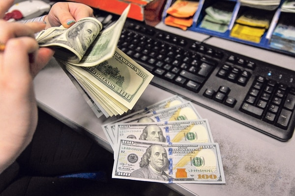 Cajera del Banco de Costa Rica cuenta divisas. Las condiciones económicas cambiaron, según explica el Banco Central, y ahora existe una presión al alza en el precio del dólar . | JOSÉ CORDERO/ARCHIVO.