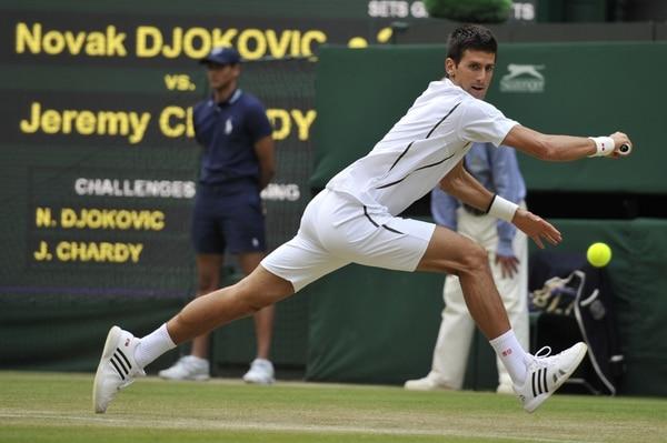 El serbio Novak Djokovic hace un esfuerzo, le llega a esta pelota y se la devuelve al francés Jeremy Chardy hoy sábado en Wimbledon.