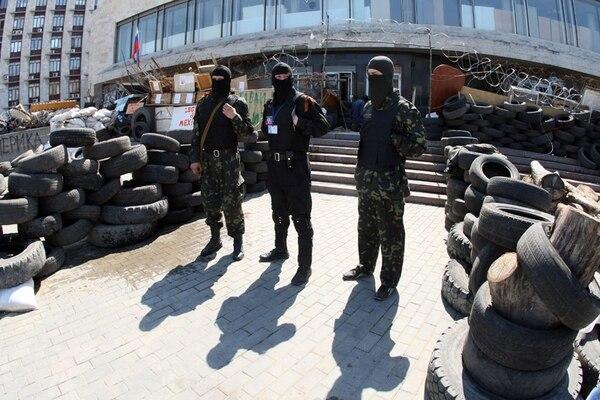 Enmascarados activistas prorrusos estuvieron de guardia por una barricada frente a un edificio estatal que fue tomado por separatistas en Donetsk. | AFP.