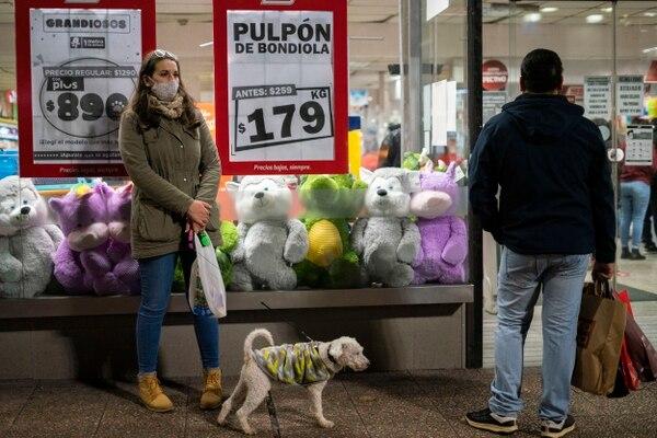 Una mujer, que usa una mascarilla protectora como medida para frenar la propagación del nuevo coronavirus, espera afuera de una tienda en el centro de Montevideo, Uruguay, el jueves 18 de junio del 2020. Foto: AFP