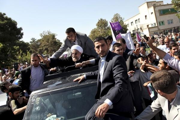 El presidente iraní, Hasán Ruhaní, saluda sus partidarios tras su arribo al aeropuerto Mehrabad, en Teherán.   AP