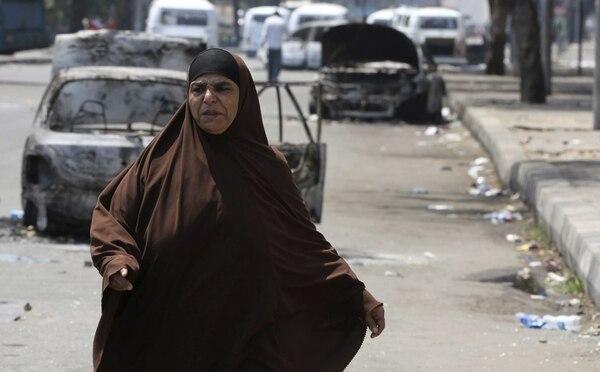 Una mujer egipcia pasa por delante de los coches destruidos durante los disturbios ocurridos esta madrugada, cerca de la Universidad de El Cairo.