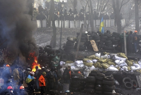 """Policías antidisturbios permanecieron posicionados delante de una de las barricadas de los manifestantes opositores en Kiev. Los manifestantes opositores ucranianos desbloquearon hoy la sede del Ministerio de Justicia, que había sido asaltado por miembros del grupo """"Causa Común"""" durante la madrugada."""