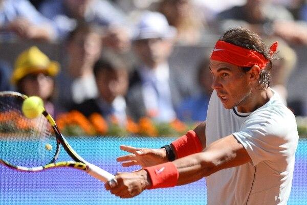 Rafael Nadal coloca este remate ante David Ferrer durante el juego de hoy en Madrid. / AFP