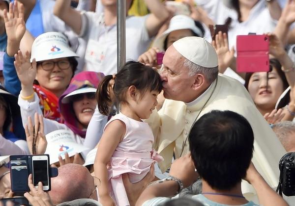 El papa Francisco besa a una niña en la frente mientras él saluda a la multitud desde el papamóvil antes de una misa, en Seúl, Corea del sur.