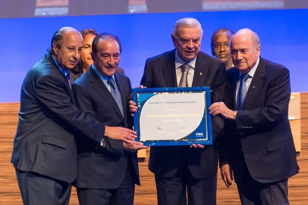 El jerarca de FIFA, Joseph Blatter (d.) entrega ayer una placa por el 100 aniversario de la Confederación Brasileña José Marín, presidente. | EFE