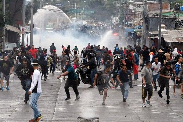 Manifestantes opositores escapaban a través de una calle de Tegucigalpa mientras la Policía los reprimía. Denunciaban fraude electoral. Fue el 18 de diciembre del 2017.