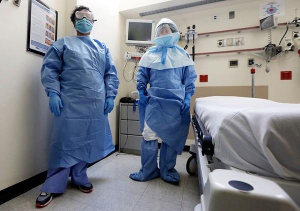 Empleados de un hospital en Nueva York, Estados Unidos, muestran los trajes necesarios para atender enfermos de ébola.   AP