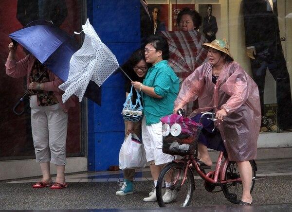 Mujeres taiwanesas sostienen sus paraguas contra las poderosas ráfagas de viento, en Taipei, Taiwán, donde también se siente los efectos del tifón Fitow.