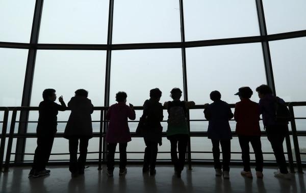Visitantes miran hacia el lado de Corea del Norte desde el observatorio en Paju, Corea del Sur.