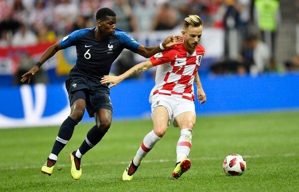 Paul Pogba trata de robarle la pelota a Iván Rakitic. Fotografía: AP.