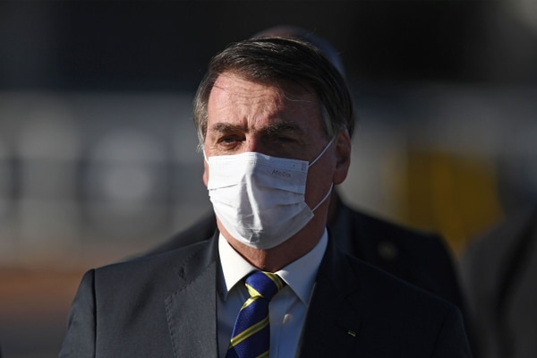(FILES) In this file photo taken on May 12, 2020, Brazilian President Jair Bolsonaro wears a face mask as he arrives at the flag-raising ceremony before a ministerial meeting at the Alvorada Palace in Brasilia, Brazil, amid the new coronavirus pandemic. - As the number of dead from coronavirus shot up in Brazil, the popularity of far right President Jair Bolosonaro has remained unchanged. (Photo by EVARISTO SA / AFP)