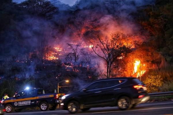 Oficiales de la Policía de Tránsito se mantienen a la expectativa ante la quema de un charral cerca del residencial Villa Real en Santa Ana, cerca de la ruta 27. Foto: John Durán