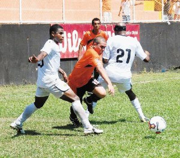 El puntarenense Ricardo García busca un espacio en medio de los liberianos Tirso Guio y Harold Wallace (27). | RONNY SOTO PARA LA NACIÓN