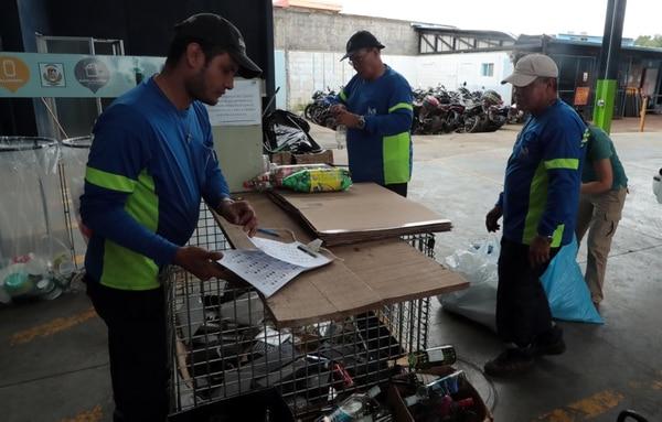 Julio Martínez (de gorra y a la izquierda) apunta las cantidades de material que las personas llevan al centro de acopio, para que se les asignen los ecolones correspondientes. Foto: Alonso Tenorio