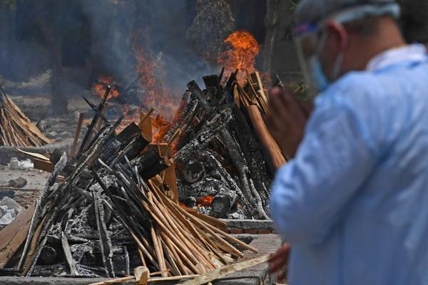 Un miembro de la familia reza junto a la pira en llamas de una víctima que murió por el coronavirus en un campo de cremación, en Nueva Delhi, el 4 de mayo del 2021. Foto: AFP