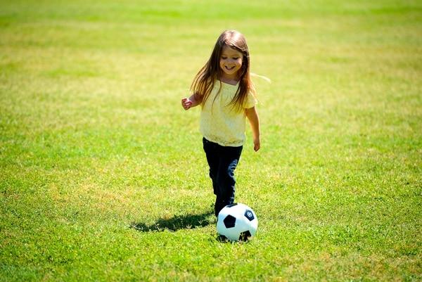 Una niña jugando fútbol y siendo feliz. Foto: pexels.com