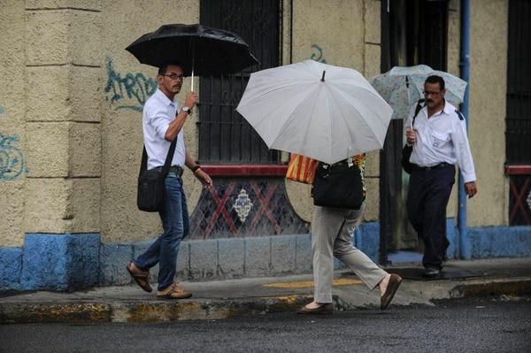 Varios transeúntes en barrio Amón, San José, estaban preparados y abrieron sombrillas y paraguas esta tarde.