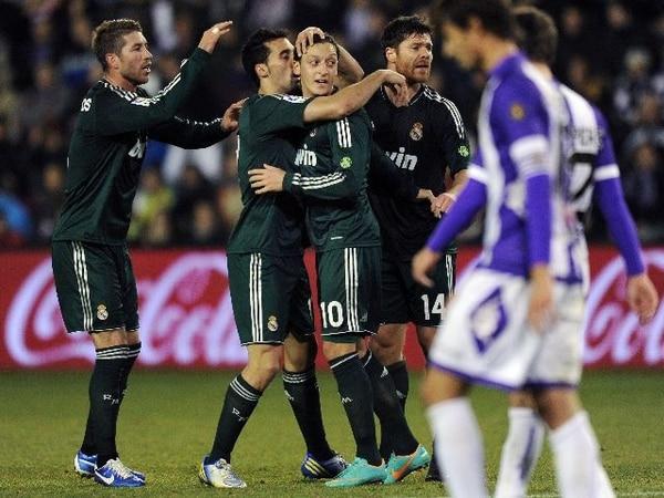 Los madridistas Álvaro Arbeloa y Sergio Ramos felicitan a Mesut Ozil. | AP