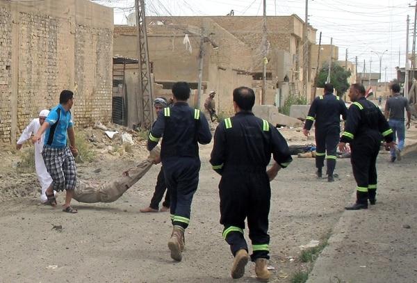 Los equipos de rescate arrastran las víctimas después de un ataque con morteros en la ciudad de Ramadi, Irak.