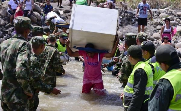 Colombianos cruzan con sus pertenencias el río Táchira para llegar a Cúcuta Colombia tras el cierre de las fronteras con Venezuela