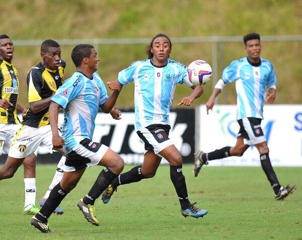 Los hermanos Jason (izq.) y Jameson Scott (centro) custodian una pelota ante Uruguay en la sétima fecha. | ARCHIVO