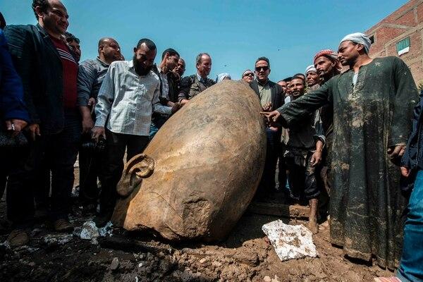 El ministro egipcio Khaled el-Anani posa para la foto con los trabajadores, al lado de la cabeza de una estatua aparecida en el distrito de Mattarya de El Cairo.