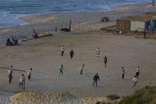Palestinos jugando fútbol en una playa de Gaza