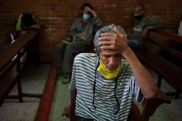A man, equipped with a protective face mask as a precaution against the spread of the new coronavirus, waits to receive a free meal at a church in The Cemetery neighborhood of Caracas, Venezuela, Friday, May 22, 2020. The number of people who come looking for food at the church has increased in quarantine. (AP Photo/Ariana Cubillos)