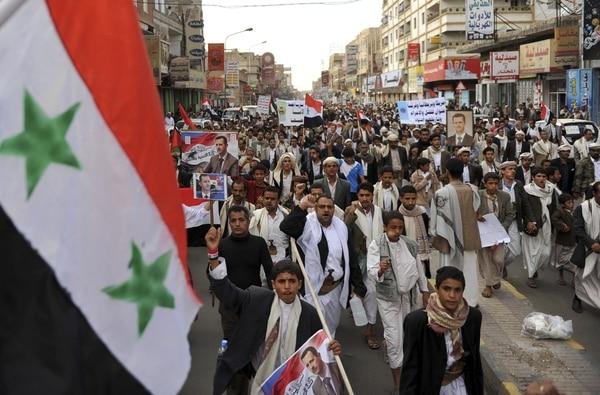 Yemeníes chiítas gritan y sujetan banderas de Siria durante una protesta contra un posible ataque militar en Siria, en Saná, Yemen.