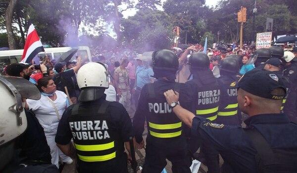 Manifestantes lanzaron bengalas a la policía en su intento por ingresar al bulevar de la Asamblea Legislativa. Graciela Solís.