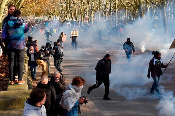 Decenas de personas evitan el humo del gas lacrimógeno durante una manifestación contra las reformas de las pensiones, en Burdeos, el 5 de diciembre del 2019. Foto: AFP