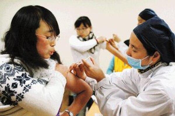 BEJ01 SHANGHAI (CHINA), 17/12/2009.- Unas estudiantes chinas reciben la vacuna contra el nuevo virus A (H1N1) de la gripe de forma gratuíta en la Escuela de Magisterio de Shanghai, China. EFE/Sherwin