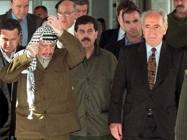 El líder histórico palestino, Yasser Arafat (izquierda), se reunió en febrero de 1999 con Shimon Peres en la Ciudad de Gaza. Peres era el primer ministro de Israel.