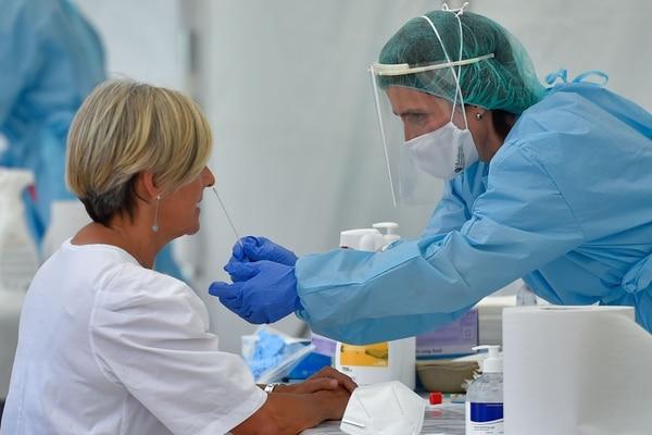 A health worker uses a swab to collect samples from a visitor to a temporary testing centre for the novel coronavirus in the Spanish Basque city of Ordizia on July 8, 2020. - Spanish authorities see the pandemic as having been essentially brought under control but are monitoring some 50 instances where new cases appear to be latent. (Photo by ANDER GILLENEA / AFP)